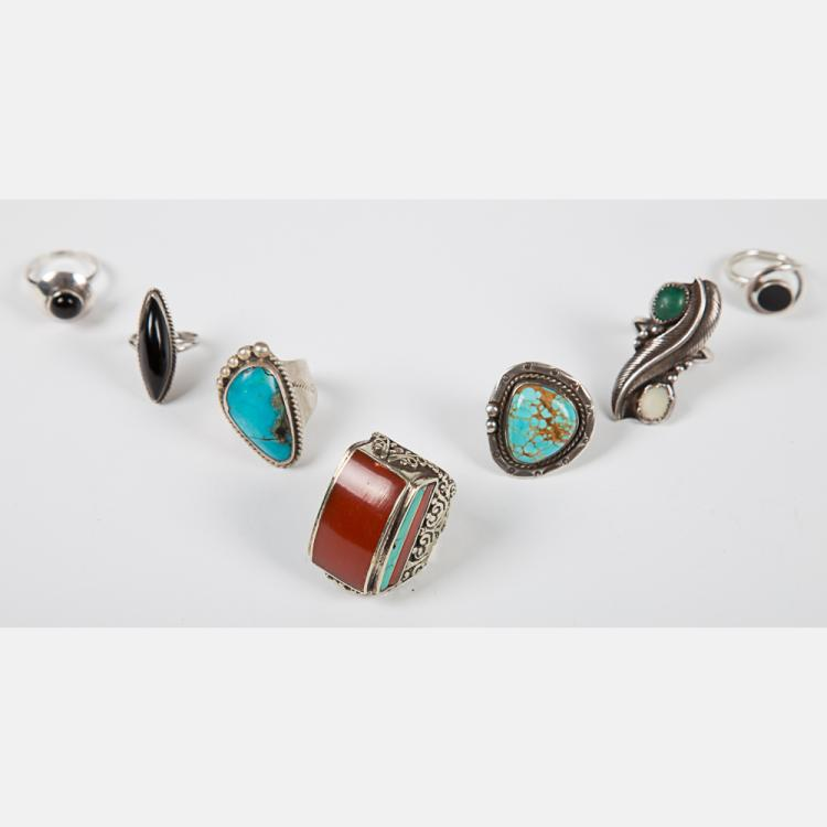 A Group of Seven Navajo Silver Rings with various semi precious stones including Turquoise, Coral and Onyx.