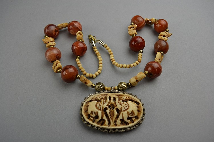 An Agate And Carved Bone Necklace Having Figural Carved Bone Elephant Form Beads Set Between By Agate Beads Suspending The Silvered Metal Set Carved Bone Pendant Depicting A Pair Of Opposing Elephants Size 24 Length