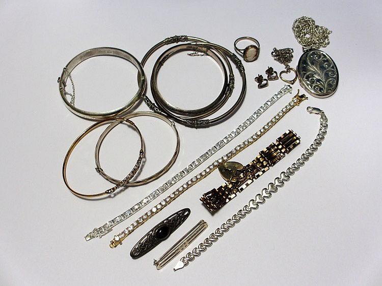 Three silver bangles, two white metal bangles, a