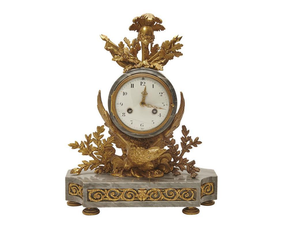 Empire Ormolu Mounted Gray Marble Mantel Clock, 19th century, the clock mounted on a winged eagle and laurel leaf base and surmounted by a war trophy finial