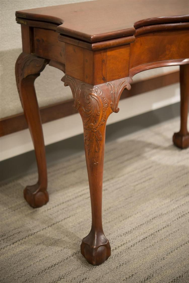 CHIPPENDALE CARVED MAHOGANY SERPENTINE FRONT LIFT TOP SWING LEG GAMES TABLE, 18th century