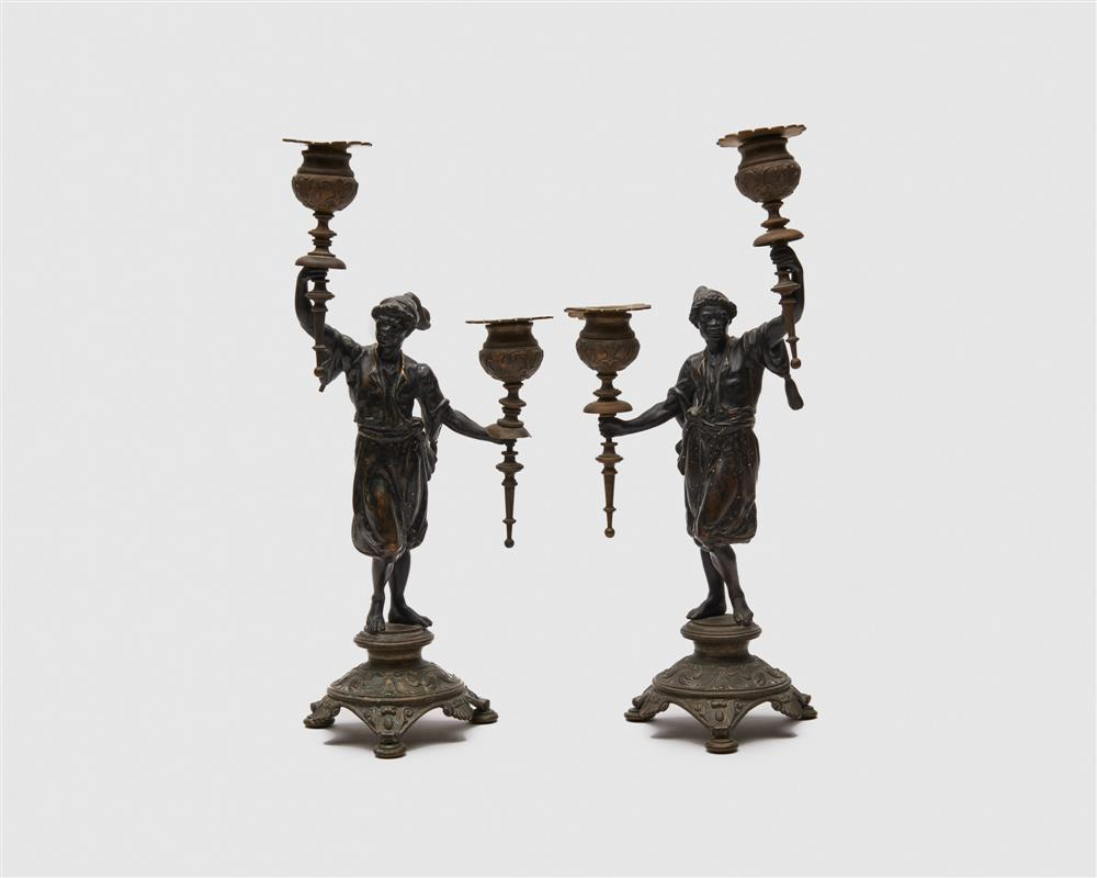 Pair of Continental Patinated Bronze Figural Two Light Candlesticks, with gilt highlights
