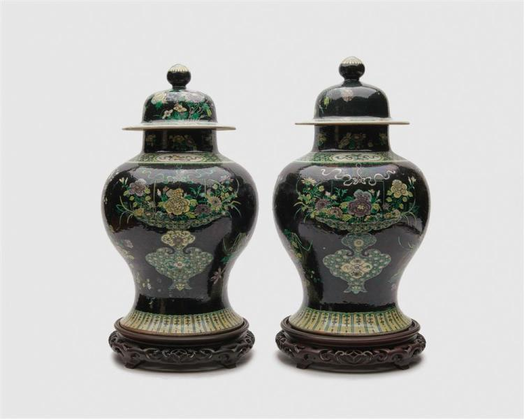 Pair of Chinese Iridescent Famille Noir Covered Baluster Jars, on carved wood stands