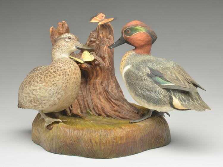 Full size carving of greenwing teal on wooden base with carved butterflies, William Koelpin.