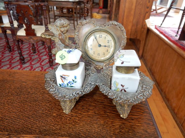 Antique, cast metal, bronze wash double inkwell holder, with 2 painted porcelain inkwells, stand has angel holding heart with wind up clock in center. COND G, appears at one time there was 2nd angel on right side?