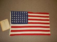 Original 48 star US flag with booklet, shows minor holes in star field
