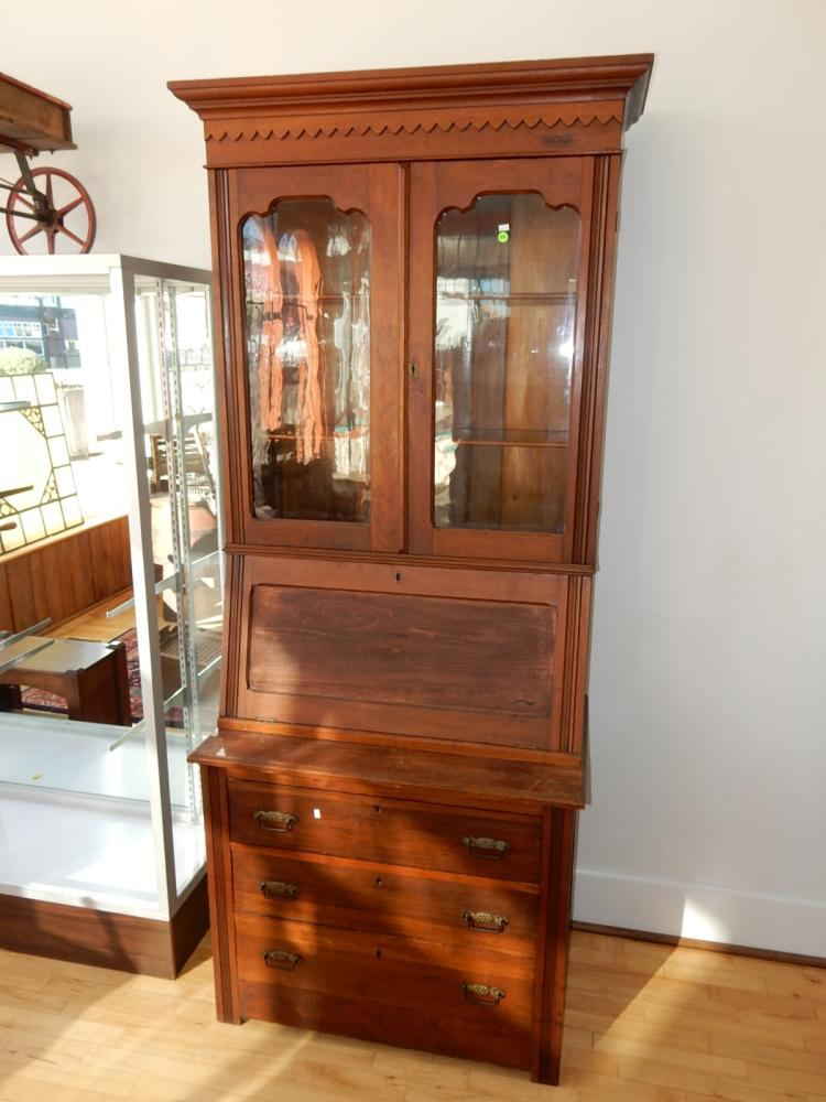 Antique Victorian walnut curio hutch with fall front desk, with old wavy glass doors. Special shipping required