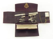 A surgeon?s pocket instrument kit by J H Montague, 101 New Bond Street, in a folding maroon leather case containing scalpel, two pairs of locking forceps, probe, needles and suture thread. CR. Very good condition, tip of scalpel snapped off, case a bit scuffed.