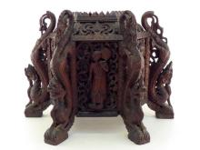 A large and impressive Burmese teak hexagonal stand, each face with a dancing or attendant figure and foliage in high relief, each apex with a tall dragon, its feet as supports for the stand. 53cm. across x37cm. high. In generally good condition, part of flames missing on mouths of four dragons.