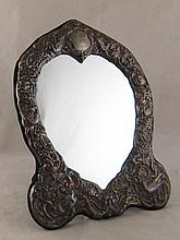 An ornately embossed silver heart shaped table
