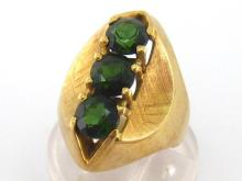A green tourmaline ring, the three uniform 6mm round cut stones vertically set above shaped and textured shoulders, the shank stamped '14k 585', finger size N/O, 8.3gms