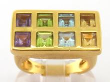 A French gentleman's multi-gem dress ring, the rectangular bezel set with pairs of square cut citrine, aquamarine, peridot, and amethyst, the shank stamped '750', French poincon to outer shank, finger size Q, 11.9gms