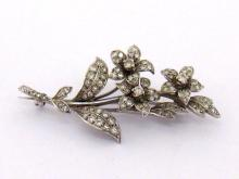 A diamond spray brooch, the three flower design set overall with small brilliants and single cuts, mounted in white metal (tests 18 carat gold), 5.5cm long, 10.3gms