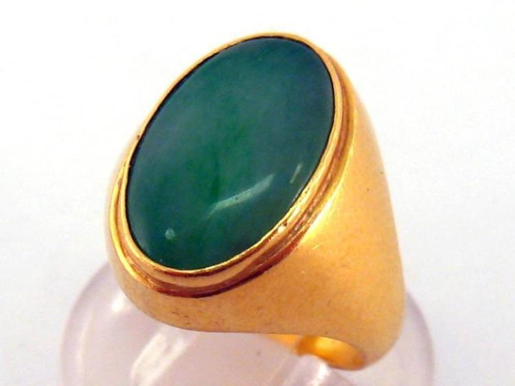 A jade ring, the oval jade tablet 14.5 x 9.5mm, rub over set, mounted in yellow metal (tests 18 carat gold), obscure marks, finger size M, 8.9gms