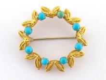 A turquoise circlet brooch, the wreath design set with small round cabochons, marked '750' verso, 3.3cm diameter, 6.4gms