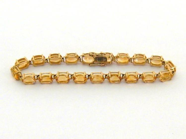 A citrine line bracelet, composed of uniform 7 x 5mm oval cut stones, to a box snap clasp, stamped '375', 17cm long, 7.4gms