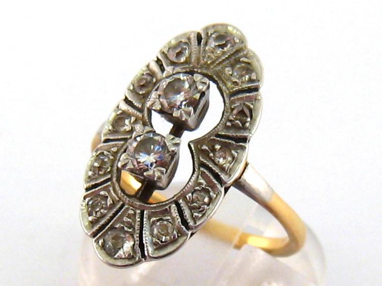 An Art Deco diamond plaque ring, the open work navette shaped bezel set to the centre with two box set brilliant cuts totalling approx. 0.34 carat, above an old cut surround, the yellow shank (tests 18 carat gold) finger size Q, 5.4gms