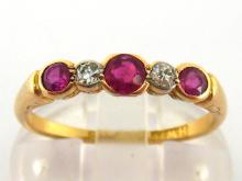 An early 20th century ruby and diamond five stone ring, composed of graduated alternate round cut rubies and brillants, the shank stamped '18ct', finger size M/N, 2.5gms
