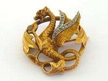 A French 18 carat gold and diamond brooch, modelled as a dragon rampant, the wings bordered with a row of small rose cuts, a small ruby set eye, twice struck with French poincon, 2.7cm wide