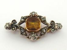 A late 19th century French topaz and diamond brooch, the central foil backed square cut yellow topaz 10.5 x 10.7mm, in an open work foliate design accented with rose cuts, mounted in gold backed silver, French import marks for 1864-1893, 4.4cm long, 10.7gms