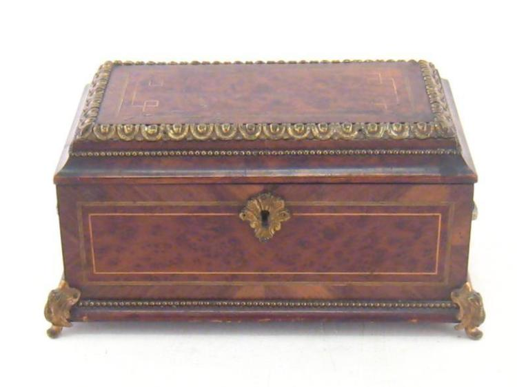 A burr walnut jewel casket with ormolu mounts . rosewood cross banding and boxwood stringing, the interior padded blue satin. 25x15x13cm.