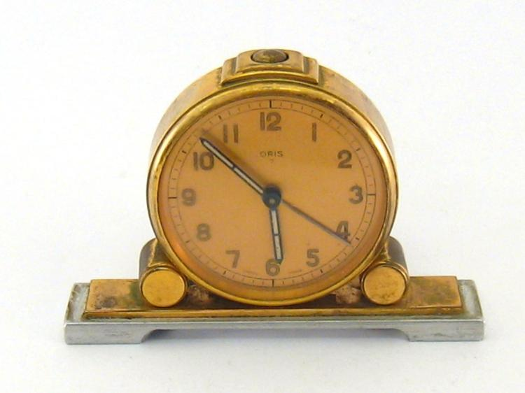 An Oris bedside alarm clock, the dial with luminous numerals and baton hands, the brass case on polished aluminium base, all in the 1930s manner.