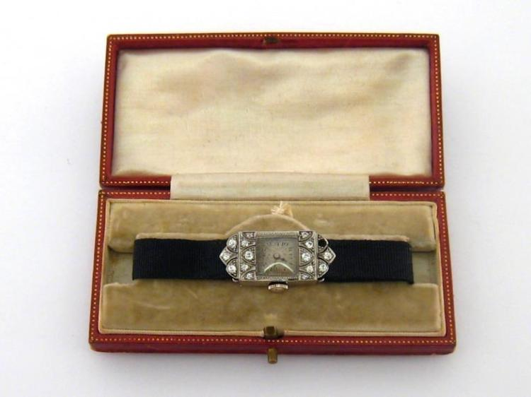 An Art Deco platinum and diamond cocktail watch, the rectangular hinged case set with small cushion cut stones (one missing), the silvered dial with black Arabic numerals, with 15 jewel manual wind movement, 14mm wide, on an adjustable black silk strap, in its original box