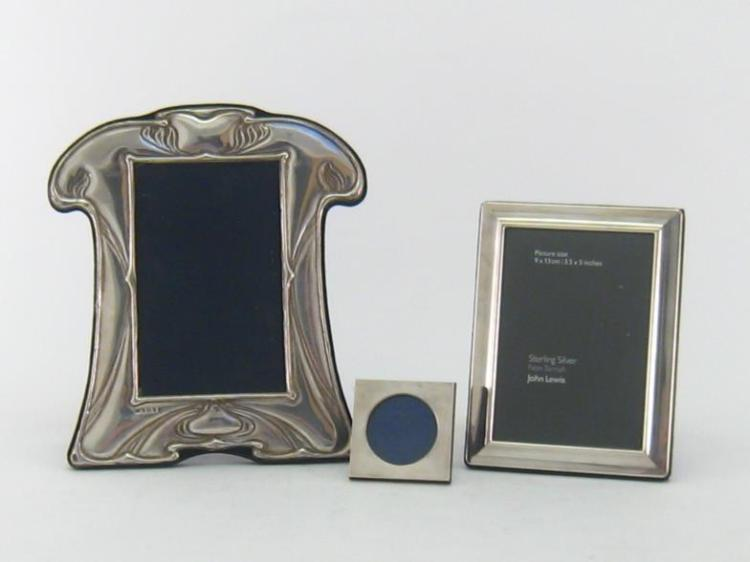 A silver-fronted photograph frame, mark of PJP, Birmingham, 1992, shaped rectangular, stamped with an Art Nouveau design, 21 cm. high; also a plain rectangular silver-fronted photograph frame, Sheffield, 2006; and a small Italian silver .800 standard square photo frame with circular aperture, Florence, pre-1968 (3)