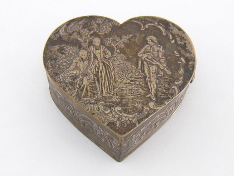 A German silver hear-shaped box, by neresheimer & Sohne, hanau, circa 1900, cover chased with two 18th century ladies being serenaded by a musician in garden setting, scroll-chased sides and gilt interior, 7.5 cm. wide, wt. 76 gm.