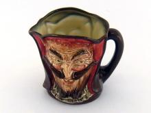 A rare Doulton Mephistopheles character mug with two faces of the devil, the base with the verse ?When the devil was sick the devil a Saint would be, when the devil got well, the devil a Saint was he.? Ht.8.5cm.
