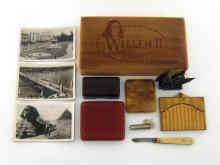 A mixed lot. A cigar box containing a small German pocket adjustable tuning device; a folding corn knife with ivory guards; three cigarette cases, one leather, one flip top plastic, one a ten compartment gilt metal example; fifteen postcards of Egypt, circa 1950s, a bakelite pin box and a model dhow