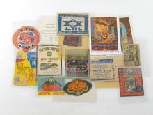 A group of 20 Israeli small prints depicting Bible stories and 14 stickers or labels of Jewish/Israeli interest including advertising labels for Mizi jam and Carmel wine, a currency rate notice from Ritz hotel in Jerusalem under Jordanian rule, pre-1967 and 2 anti-Semitic labels depicting a skull and legend