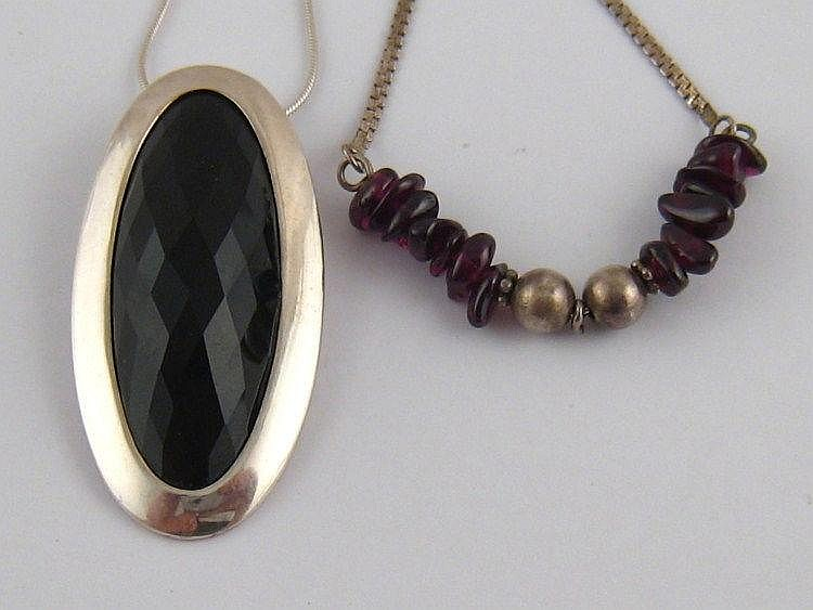 A silver pendant and necklace.