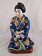 A ceramic kneeling Japanese figure in brightly
