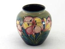A Moorcroft vase, a design of lilies on a pale green ground shading to deep blue. ?Moorcroft? and ?Made in England? stamps with blue WM signature. Ht. 12cm.