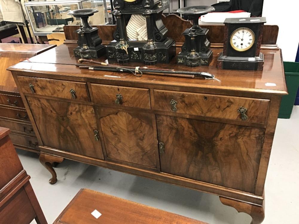 20th cent. Walnut veneered sideboard, three drawers above three cupboards on club feet.