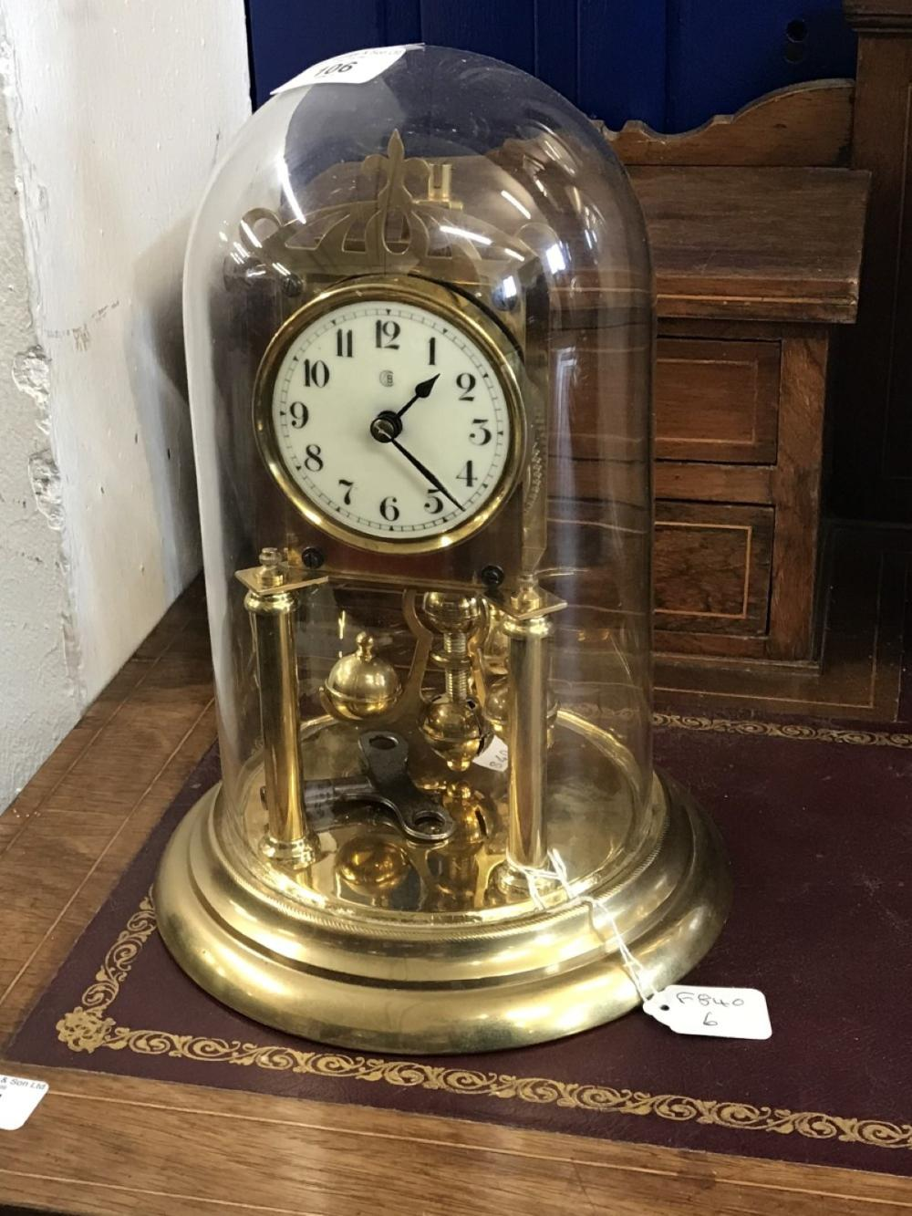 20th cent. Anniversary clock, under glass dome, enamel dial, Arabic numerals. Makers mark Bidische U