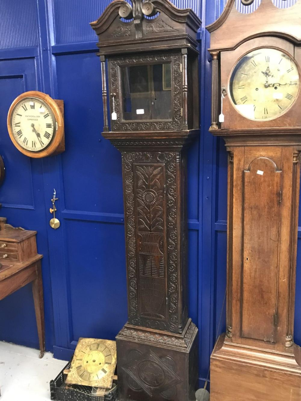 Clock: 18th cent. Oak brass faced unsigned longcase with later elaborately carved case. (Dial 11ins.