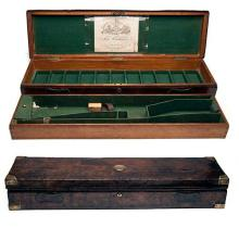 CHAS LANCASTER A BRASS-BOUND TWO-TIER OAK AND LEATHER SINGLE PERCUSSION GUNCASE,