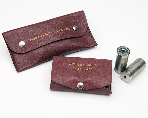 JAMES PURDEY & SONS TWO PAIRS OF LEATHER CASED 12-BORE SNAP-CAPS,