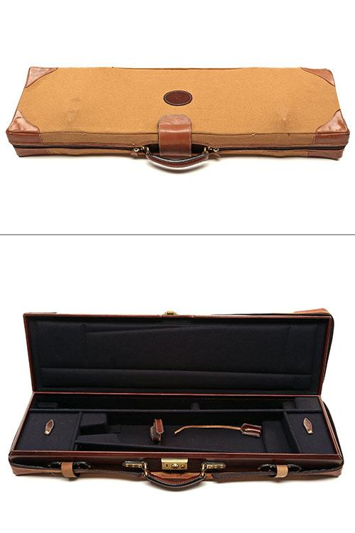 A GOOD QUALITY SINGLE LEATHER GUNCASE WITH CANVAS AND LEATHER OUTER,