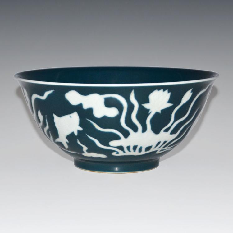 明 宣德 霁蓝釉留白刻花荷池游鱼纹碗 Ming, An Unusual Blue Glazed Deep Bowl with Relief Carved Lotus Pond Motifs in White Reserve