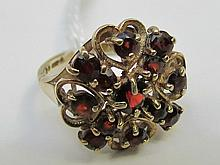 A 9ct yellow gold garnet dress ring in a cross and