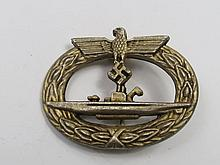A Nazi U boat badge, the vessel on an oval wreath.