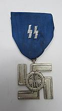 A Nazi SS medal, white metal swastika with oak