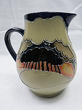 A Moorcroft pottery jug with landscape design by
