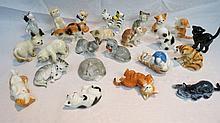 Twenty four cat figurines in various postures,