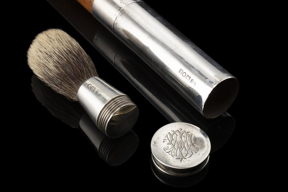A malacca walking stick with silver handle enclosing a shaving brush. Londra, 1925, S.J. silversmith (L. cm 93)...