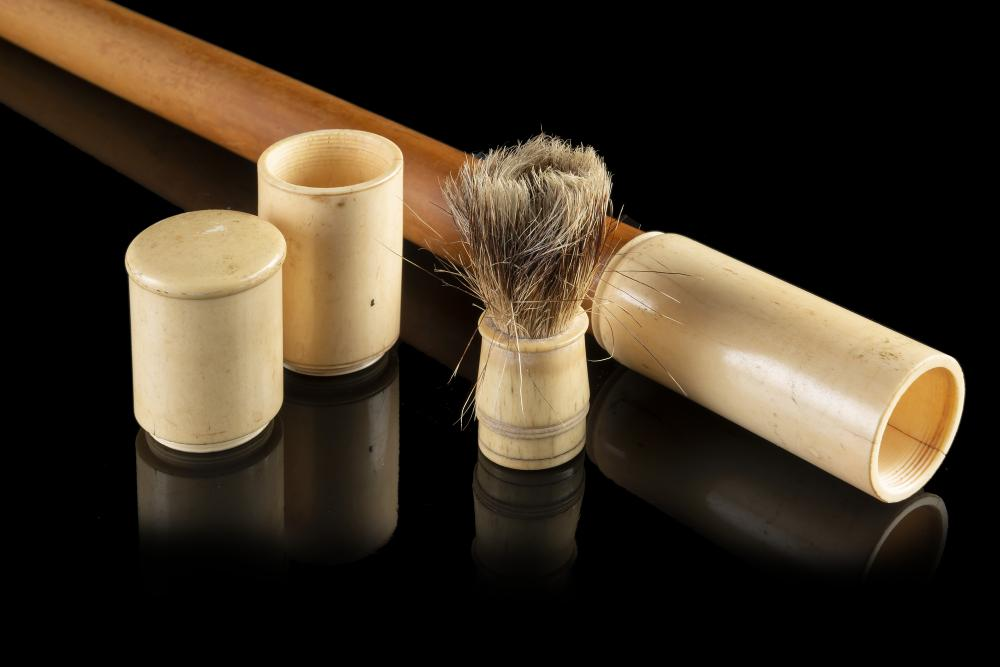 A 19th-century malacca barber walking stick with ivory handle enclosing a brush with ivory handle and shaving soap (L. cm 86) (defects) This lot may be subject to Import/Export restrictions due to CITES regulations in some extra UE countr...