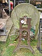 An old grindstone on cast iron stand